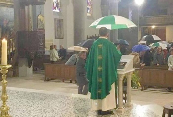 Cha xứ che dù dâng thánh lễ